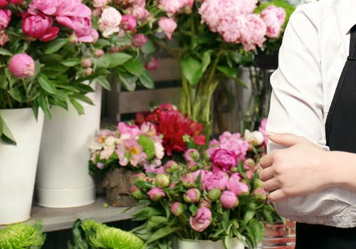 An aproned florist poses confidently in front of her wares